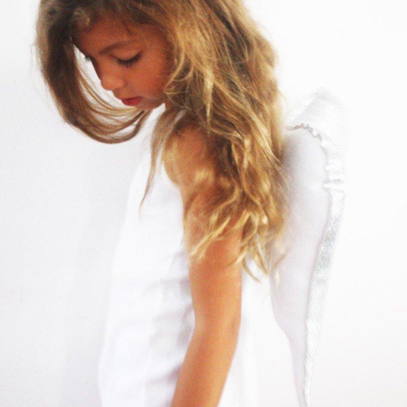 Petite fille portant les ailes d'ange à bretelles