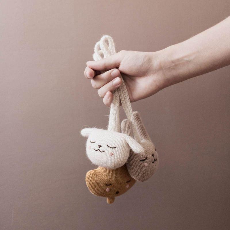 Suspension hochet | Agneau par Main Sauvage dans une main